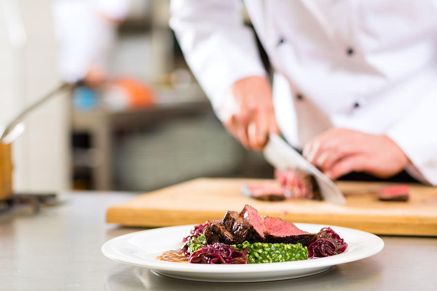 Kokk skjærer kjøtt til servering
